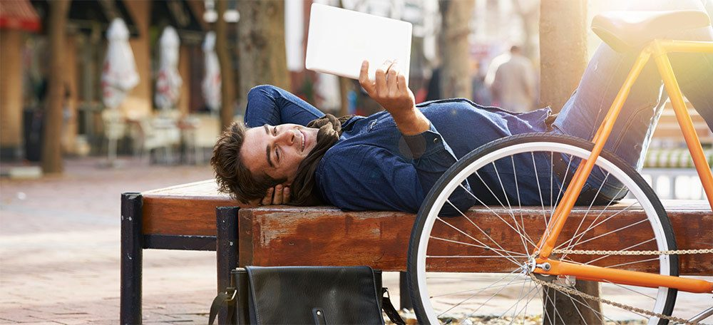 Man laying on a bench using his tablet